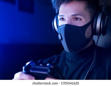 ヘッドホンでサージカルマスクを着用してビデオゲームをプレイしている男性。コンセプト:コロナウイルス(COVID-19)の自己隔離ビデオゲームをプレイする時が来ました。