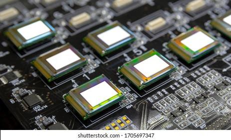 Varios micropantallas brillantes de color blanco en la estación de prueba. Los monitores brillan intensamente de cerca de color blanco. Arco iris en la superficie. Microelecrónica. Tecnología de pantalla y panel de luz.