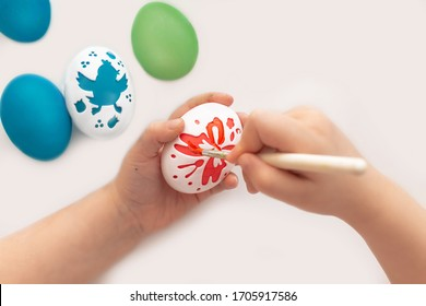 Children's hands of a girl draw shapes on eggs with a brush. happy Easter. Paint the eggs with bright colors.Draw a picture on the eggs for the holiday. Mock up