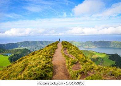 Een pad dat leidt naar gezichtspunt Miradouro da Boca do Inferno in Sao Miguel Island, Azoren, Portugal. Verbazingwekkende kratermeren omgeven door groene velden en bossen. Toerist aan het einde van de schilderachtige weg.