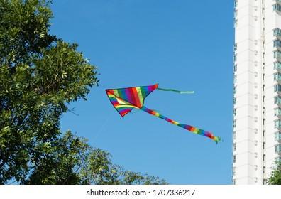 美しい明るい虹色のシンプルな凧が、白い建物の背景を持つ夏/春の天気の良い日に空を飛んでいます。楽しいアウトドアアクティビティのコンセプト。