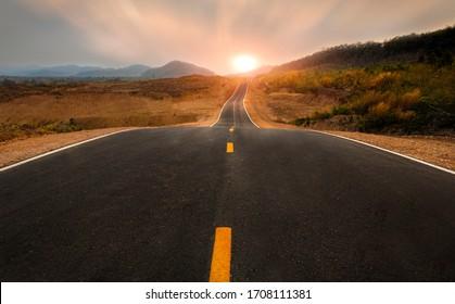 Malebná scéna krajiny, dlhá rovná cesta vedúca k hore a západ slnka na panorámu.