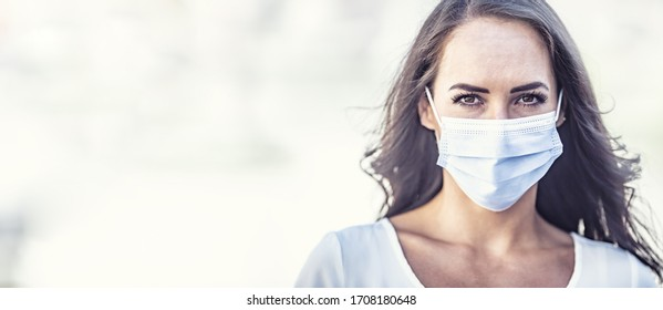 Serious looking young woman wearing a disposable face mask on an isolated background, covering the right half of the picture.