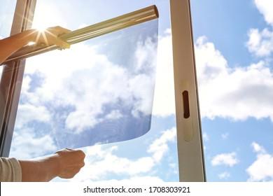 getöntes Glas im Haus. Verdunkelung des Fensters durch dunklen Film. Hände tragen Farbtonfilm auf das Fenster auf. Farbton Film auf Himmel Hintergrund. Himmelsblick durch getöntes Glas