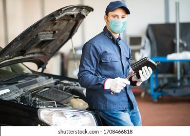 コロナウイルスのパンデミック中にモーターオイルの水差しを保持しているマスクされた自動車整備士