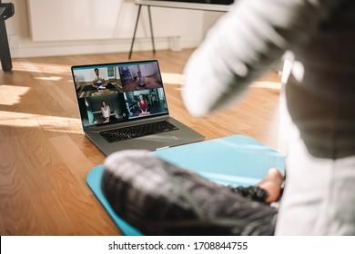 Weergave van een vrouw virtuele fitnessles uitvoeren met een groep mensen thuis op een videoconferentie. Fitnessinstructeur die online yogalessen volgt via een videogesprek op laptop.