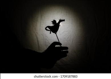 Chinesisches Schattentheater für Kinder, projiziert auf ein Betttuch, thematisiert von Saint George, 23. April. Die Schatten sind aus Pappe, Sie können die Hand sehen, die sie manipuliert. Drache, Geschichten, Geschichtenerzähler