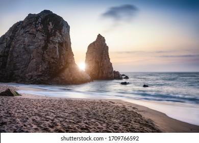 Sonnenuntergang am Ursa Beach Sea Stack, Portugal. Atlantik Schaumige Wellen, die zum Sandstrand rollen. Ferienurlaub Landschaftsszene