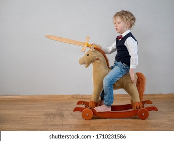 Funny child in white shirt with bow-tie, on toy rocking horse with wooden sword. boy dreams of battles, victories and adventures. concept of education of spirit, education of morale, patriotism