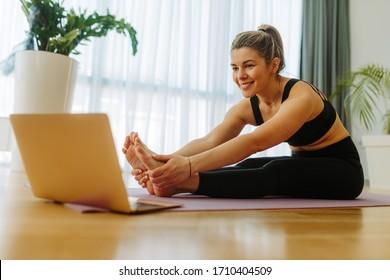 自宅のマットの上に座って前に折りたたむヨガの練習をしている若い女性のクローズショット。COVID 19のパンデミックにより、若い女性がオンラインヨガコースを見ています。