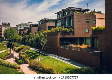Modernos edificios residenciales en la zona verde pública. Casas de apartamentos en Europa. Hermosa vista de casas inmobiliarias en Milán, Italia. Distrito comercial en verano. Área para caminar con árboles y césped.