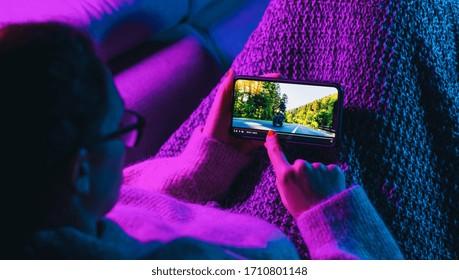 女性は架空のビデオプレーヤーサービスで携帯電話で映画を見るのをやめます。オンラインビデオストリーミング映画およびシリーズの概念。