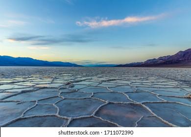日没時のバッドウォーターベイシン。塩の地殻と雲の反射。デスバレー国立公園。米国カリフォルニア州