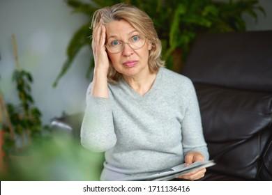 Geschokt, vrouw leest slecht nieuws van de krant