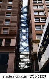 Eine lange Fluchttreppe zwischen zwei alten Gebäuden in der Innenstadt. Erinnert an Peter Parker in einer New Yorker Gasse oder West Side Story.
