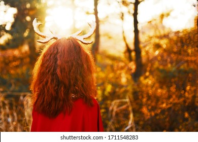 Woman in long red dress with deer horns in fall forest and looking through magic herbs to the sunset. The concept of halloween and fairy tale.