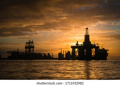 Oil Rig Platform in the water at dock in harbor, at sunrise with dramatic sky