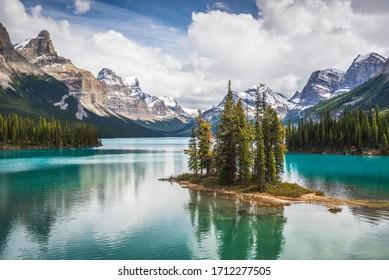 Die berühmte Geisterinsel des Maligne-Sees im Jasper-Nationalpark von Alberta, Kanada. Lebhaftes blaugrünes Wasser des Gletschersees scheint im Sonnenschein um die berühmte Ansammlung von Kiefern.