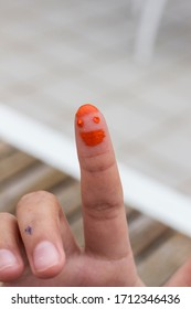 drawing of a face on a finger with orange strokes.