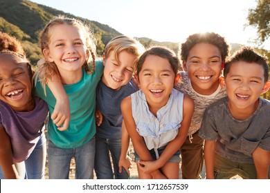 Porträt von multikulturellen Kindern, die zusammen mit Freunden auf dem Land rumhängen