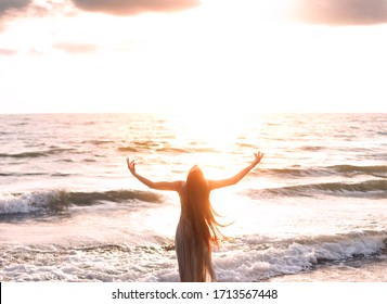 glückliche Frau steht Küste abgewandt Hand zum Himmel Himmel Sonnenlicht erhoben. Dame Mädchen genießen sonnige Sonnenuntergang Meereswellen. Konzept Hoffnung göttliche Gebetsfreiheit. Brünette lange Haare flattern Fliegenwind. Georgia