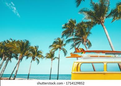 Oldtimer geparkt am tropischen Strand (Meer) mit einem Surfbrett auf dem Dach - Urlaubsreise im Sommer. Retro-Farbeffekt
