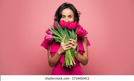 Internationaler Frauentag. Extrem glückliche Frau in einem leuchtend rosa Kleid riecht an einem Blumenstrauß, den sie in ihren Händen hält.