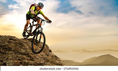 Ciclista en bicicleta por la roca al amanecer en las hermosas montañas en el fondo. Concepto de ciclismo de enduro y deporte extremo.