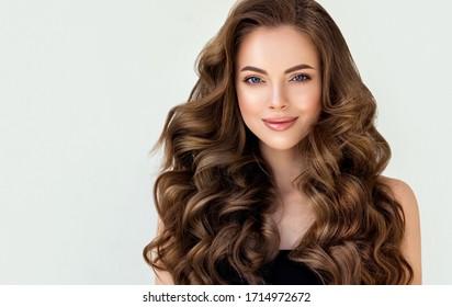 長い巻き毛の美しい笑いブルネットモデルの女の子。笑顔の女性の髪型波状カール。赤い爪のマニキュア。ファッション、美容、メイクのポートレート