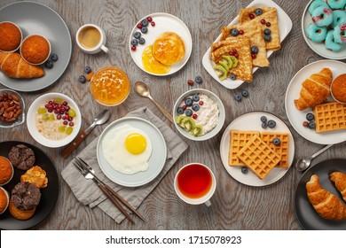 Continentaal ontbijt van bovenaf vastgelegd (bovenaanzicht, plat). Koffie, thee, croissants, jam, ei, pannenkoeken, maffins en havermout. Houten achtergrond. Familie ontbijttafel.