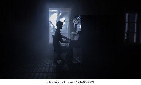 夜に家具と窓のあるリアルなドールハウスのリビングルーム。暗い部屋で古いピアノに座っている男。セレクティブフォーカス。