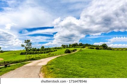 Grüne Hügelpfadhimmelwolken. Rad zum grünen Hügel. Grüne Hügelstraßenlandschaft