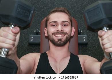 上からの眺め。ジムで横になっているダンベルでベンチプレスをしている若い男