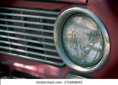 ビンテージ車のヘッドライト。赤い色の古い車。ヴィンテージカーボディ