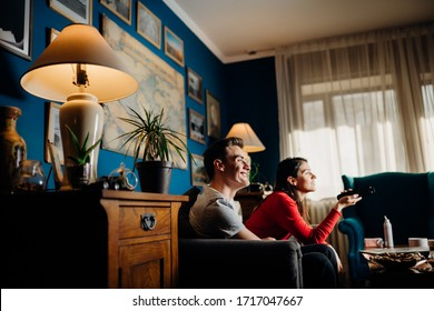 Happy couple at home watching TV together.Remote control fight.Watching favorite show/film.Fun comedy movie.Binge watching television.Relationship home quarantine lockdown time.Streaming service