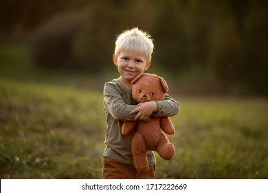 Little boy on a walk in the park stands smiling and hugs his teddy bear friend. Image with selective focus and toning. Image with noise.