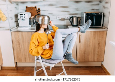 Home duties while quarantine and self-isolation. Young woman is cooking in the kitchen while quarantine. Woman with saucepan on head.