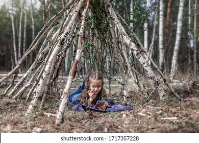 Young girl chatting on mobile phone in the built wooden stick hut house in the wild birch forest during her social distant walking in lockdown time, walking on fresh air, outdoor active lifestyle