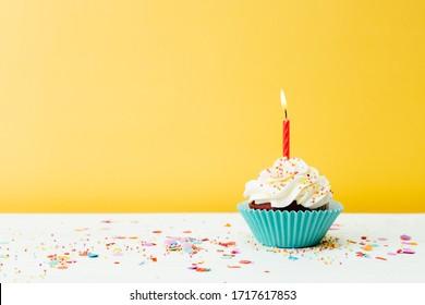 Un colorido cupcake de cumpleaños con una vela y confeti sobre un fondo amarillo