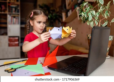 Nettes kleines Grundschulmädchen, das Origami-Fisch mit gefaltetem Farbpapier macht Video auf Laptop, Online-Workshop, Aktivität zu Hause, Kreativität und Fernunterricht, Fokus auf Fisch