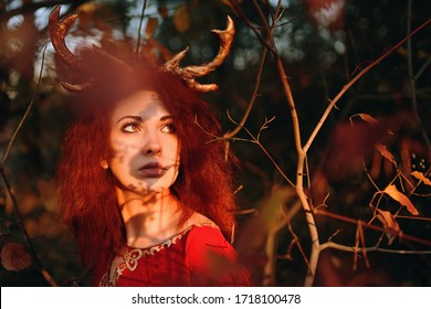 Red-haired Woman in long red dress with deer horns in autumn forest and looking for magic herbs. The concept of a fairy tale halloween