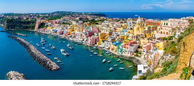晴れた夏の日、ナポリ、イタリアのプローチダ島のカラフルな家とコリチェッラ村の港のパノラマビュー
