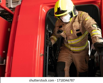Firefighter getting down from the truck equipped with an intervention suit, helmet and mask to protect himself from the covid 19