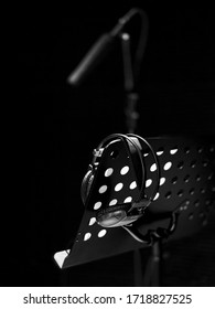 This black and white photo was taken in a professional voice recording studio, featuring a microphone and headphones.