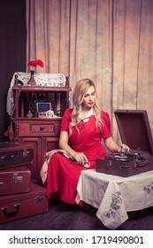 a blonde woman in a vintage red dress in a retro interior plays music on an old gramophone