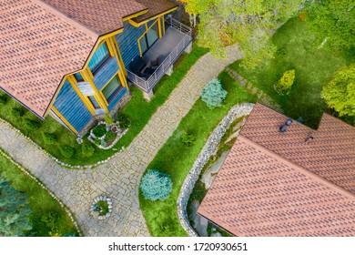 家の領土は平面図です。2つの家の間の石の道。コテージの村の領土は石で飾られています。木で作られたカントリーハウス。コテージの屋根のドローンビュー