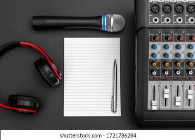 Notepad with audio sound mixer, microphone and headphones on black. Top view. Space for text.