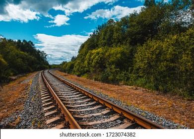 日没時の美しい色とりどりの空を背景にした鉄道駅。鉄道のある産業景観、夏には雲のある青い空。夕方には鉄道のジャンクション。鉄道プラットフォーム。交通手段