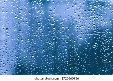 rain drops on a blue window glass transparent surface. water droplets on windowshield in a rainy days in autumn spring summer winter in night. stormy weather. loneliness sad depression concept.