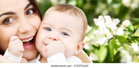 family and motherhood concept - happy smiling young mother with little baby over natural spring cherry blossom background